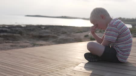 szeplők : The child is sad at sunset by the sea. The boy sits on the waterfront and thinks about something. Stock mozgókép