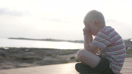 kypr : Upset child on a walk in the park by the sea. Offended boy crying at sunset Dostupné videozáznamy