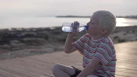 nyel : A blond boy drinks water from a bottle. The child sits on the waterfront watching the sunset and drinks water