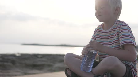 nyel : A child drinks water from a bottle on the background of a sunset in the sea. A blond boy is sitting on a wooden quay, he raises a plastic bottle to his face and slowly drinks water