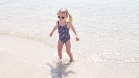 горох : fashionable little girl in a bathing suit out of the sea. Baby on the sea on a hot summer day in Cyprus