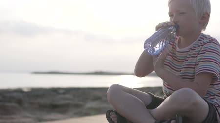 nyel : The boy drinks water at sunset by the sea. The child drinks water from a plastic bottle. Stock mozgókép