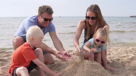 hayran olmak : Family on the beach by the sea. Young family with children stands sand castle on the beach Stok Video