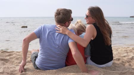 hayran olmak : Happy Family Sits On the beach watching the sea. Husband with wife and their children hugging on the beach Stok Video