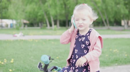 mluvení : Little girl blonde talking on a toy phone in the park in spring.