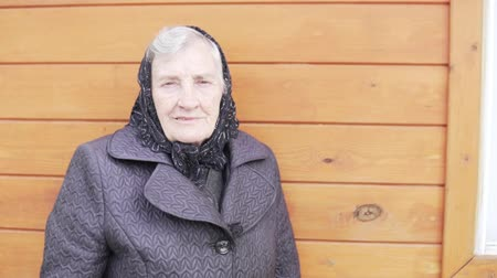 luto : An old grandmother in a black headscarf is standing at a house in the village and smiling. Russian grandmother goes to the wake