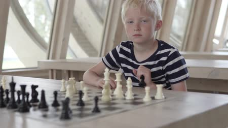 delikanlı : Handsome blond boy playing chess. The boy is waiting for the opponents move. Stok Video