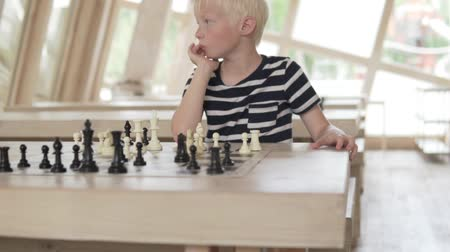 острый : Handsome blond boy playing chess. The child thinks over the course. The camera smoothly approaches the young player.