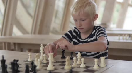 delikanlı : The boy plays chess. The child sits at a table with figures, the camera approaches it and the focus goes to the board Stok Video
