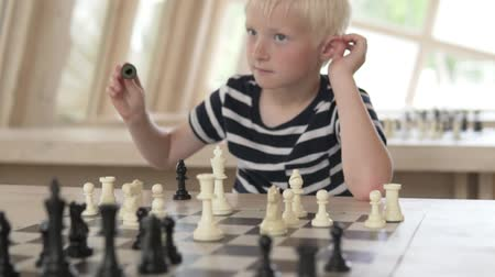 darling : The child plays chess. The boy plays with white pieces. The camera approaches the table and the focus goes to the chessboard with figures.