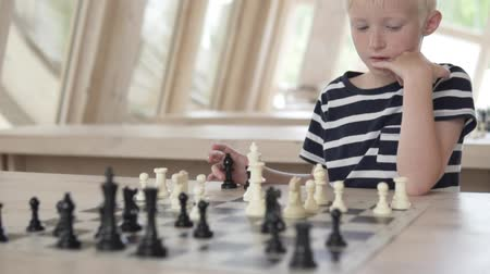 darling : Serious Handsome boy blond playing chess. The child is focused and thinks over the course. The camera smoothly approaches the young player and moves to the chessboard.