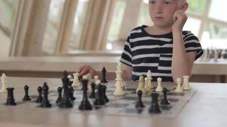 умный : The boy plays chess. The child sits in a spacious bright chess club and waits for the opponents turn.