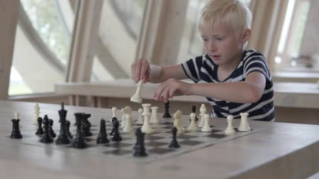 острый : Handsome blond boy playing chess. The boy sits in a chess club and solves the problem. He moves the figures