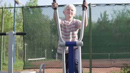 tornacipő : A blond boy plays sports on a simulator on the street. A child plays on the playground in the park. The boy goes in for sports on an elliptical trainer in the park in summer Stock mozgókép