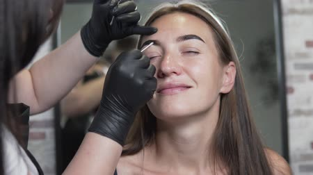 hůlky : Woman makes bright eyebrows with beauty salon. Browmaster removes the eyebrow paint with a wet cotton swab