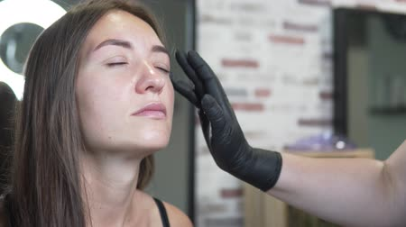 мастер : Eyebrow correction in a beauty salon. Beautician applies moisturizer to the eyelids of a young woman