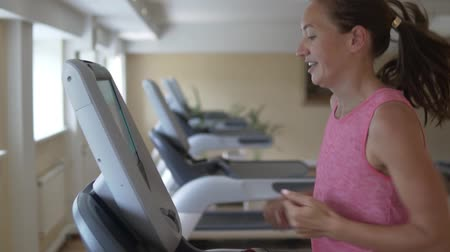 kulturystyka : young woman running on the treadmill simulator in the gym. Cardio training in a fitness club on a treadmill Wideo
