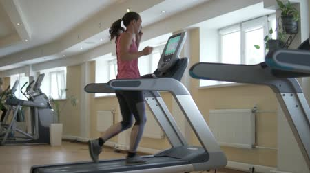 кавказский : Young woman increase speed on treadmill and running.