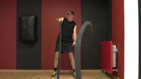 functioneel : The man in the gym is engaged in cross fit. A man pulls a rope for functional trening.