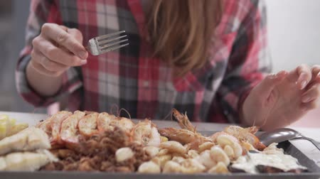 meze : Woman eating seafood in a cafe. Close-up of a plate of food. Stock Footage
