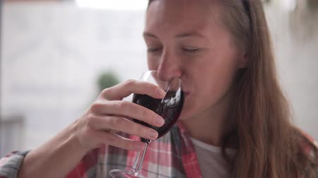szomjúság : A young woman drinks red dry wine from a glas. Stock mozgókép