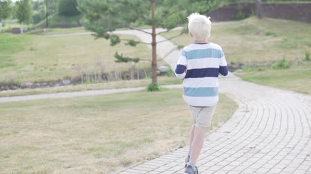 гонка : A handsome blond boy is running through the park. Child jogging in the summer park Стоковые видеозаписи