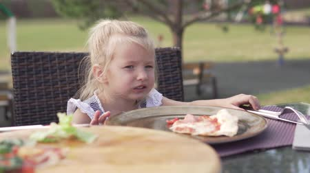 mastigação : Hungry little girl eating pizza in a cafe on the street on a hot summer day. Baby sits on a table in a cafe and chews delicious pizza