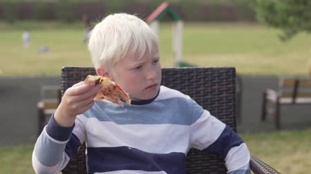 mastigação : boy blond eats pizza in a street restaurant. He sits at a table on the street and chews delicious pizza with ham and cheese with appetite.