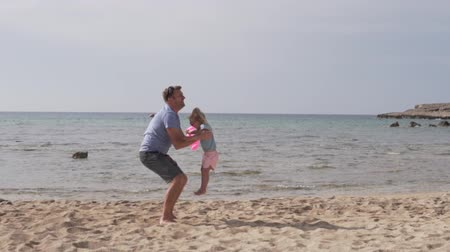 szépen : Slow motion of handsome father throwing his adorable daughter in the air. Dad plays with his daughter on the beach by the sea, a man throws up the baby in the top
