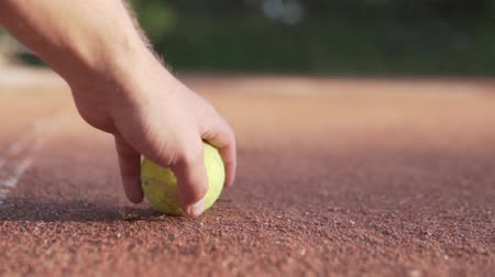 árbitro : Tennis court lies on the clay court. Blurred players in the background. Hand throws a ball on the court Vídeos