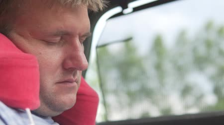 nostalgia : A handsome man is sleeping in a car on a traveling pillow. Rear passenger in the car is sleeping Stock Footage