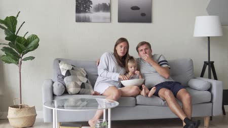 pipoca : The family is watching TV, eating popcorn and laughing. A baby sits between her parents hugging them and they kiss. Gentle morning video of the family on the couch