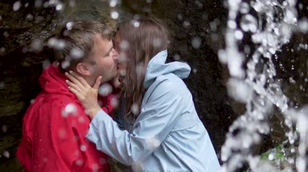 romantik : A couple in love is kissing under a waterfall. A couple of tourists gently kisses under the water of the waterfall. Slow Motion, Wildlife, Altai Stok Video