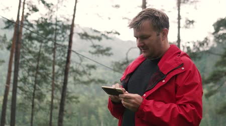 rain forest : A man in a forest near a mountain river is looking at a mobile phone. Wildlife, mountain under the Altai, Russia. Rainy morning hiking without internet