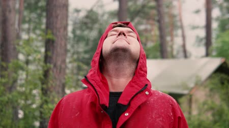 обмотка : A man in a hood in a red jacket standing in the rain in the forest. Close-up face, slow motion Стоковые видеозаписи