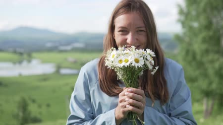 plášť : Young woman in a raincoat walks on the field with flowers. She is holding a bouquet of wildflowers and pulling them into the camera. Focus on colors