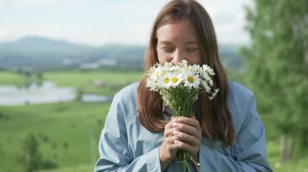plášť : Young woman in a raincoat walks on the field with flowers. She is holding a bouquet of wildflowers and pulling them into the camera. Focus on colors. Slow shooting Dostupné videozáznamy