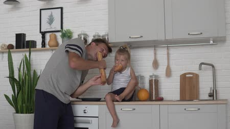 bagietka : Funny dad feeds his little daughter bread in the morning in the kitchen. Wideo