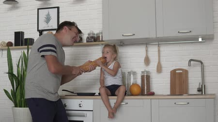 psycho : Morning dad and his little daughter in the kitchen. A man plays with a child while he is preparing breakfast, he sings in a loaf of bread, as if it were a microphone and laughs