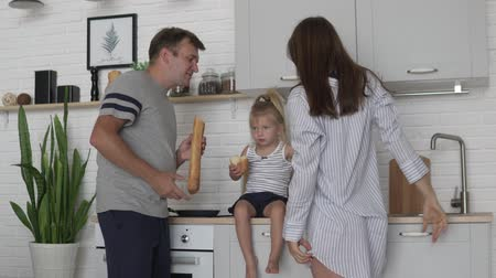 楽しんで : Family in the kitchen in the morning. Dad with a small daughter eagerly eats bread, his wife comes and gently kisses her husband. Womens day, a man prepares breakfast 動画素材