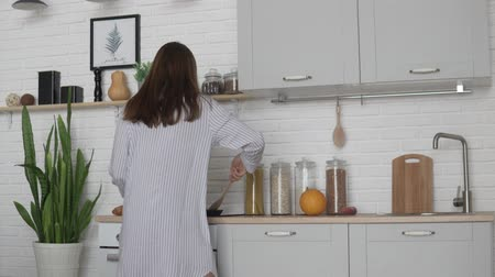 feliz : Young woman in nightie prepares breakfast in the kitchen in the morning. a cheerful man comes to her and kisses her Vídeos