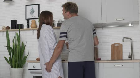 feliz : Cute morning lovers in the kitchen. A woman prepares breakfast, a man brings her something and kisses his beloved wife Vídeos