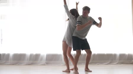 home studio : Slow motion of cute couple dancing in the bedroom, jumping and laughing together having fun on weekend morning
