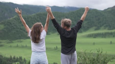 алтай : Man and woman standing on the edge of beautiful canyon, victoriously outstretching arms up. A couple in love raises hands and pulls them to the sky.
