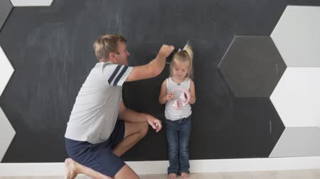flat head : Father measures the growth of a small daughter. The baby is standing against the wall and the man makes a chalk mark on her head Stock Footage