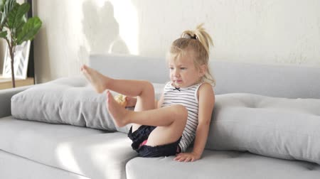 bagietka : A child with bread is sitting on the sofa and is chewing a white loaf.