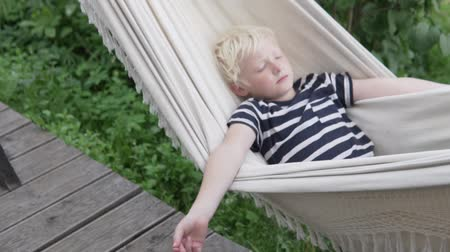 len : Happy boy blond sleeps in hammock in summer at the cottage Stock mozgókép