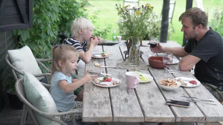 veranda : The family has lunch on the veranda in summer. Dad with children eating in the country