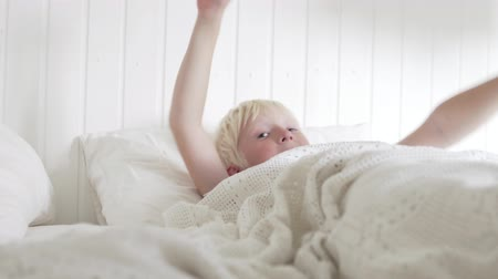 waking : Cute boy wakes up in the morning in a white bed and sipping. Stock Footage