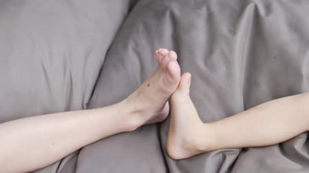little : Childrens feet are kicking each other on pillows. Brother and little sister play with their feet Stock Footage